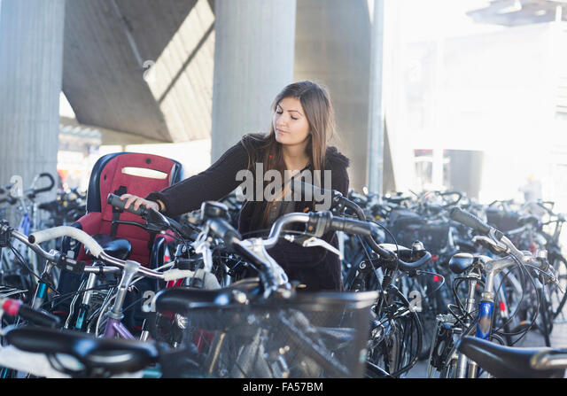 Young woman parking her bicycle, Freiburg im Breisgau, Baden-Württemberg, Germany - Stock Image