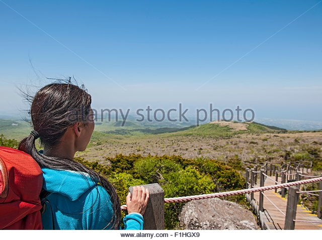 Hiker enjoying the view on the way to Hallasan, the highest mountain in Korea, Jeju Island, South Korea - Stock Image