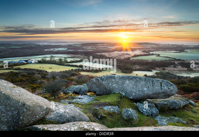 A frosty early spring sunrise looking out over a patchwork of fields and rolling hills at Helman Tor a rocky outcrop - Stock-Bilder
