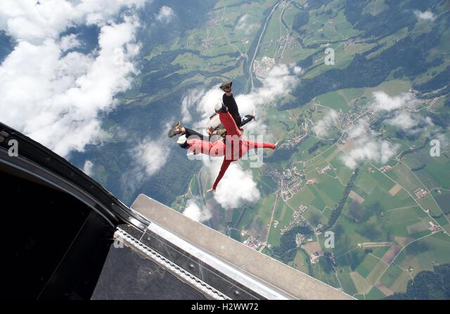 Tandem master takes woman on her first parachute jump over Gruyeres in Switzerland. - Stock Image