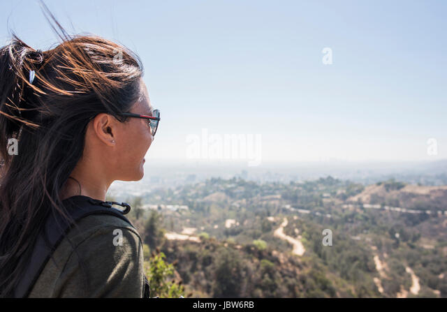 Young woman looking out at landscape from Hollywood sign, Los Angeles, California, USA - Stock-Bilder