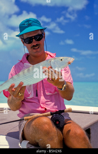 salt water fishing angler in flats fishing boat holds trophy bonefish tropical fishing bright colors - Stock Image