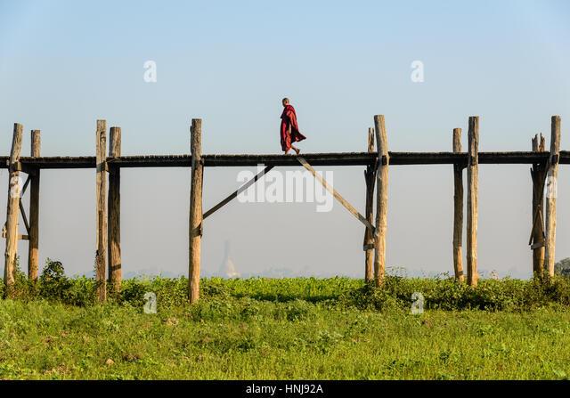 AMARAPURA, MYANMAR - FEBRUARY 20, 2014: monk walking over U Bein Bridge, the world's longest teakwood bridge - Stock-Bilder