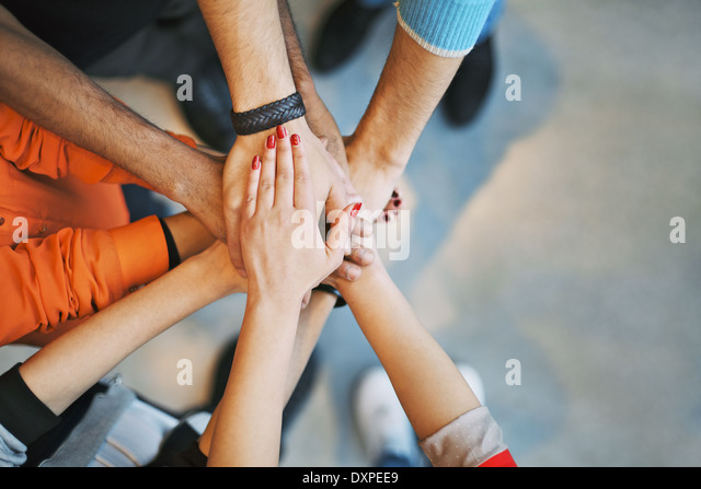 Multiethnic group of young people putting their hands on top of each other. Close up image of young students stacking - Stock Image
