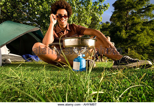 Young man, in sunglasses, cooking food on gas camping stove, smiling, front view, portrait surface level - Stock Image