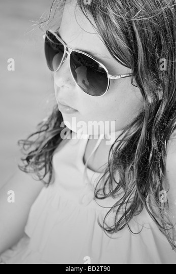 Black and White Shot of a Young Girl in Sunglasses by the Pool - Stock Image
