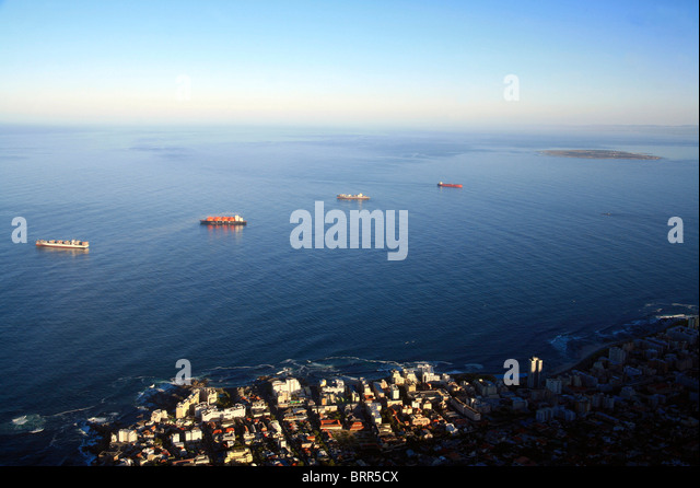 Boats anchored in Table Bay with Robben Island in the distance - Stock Image