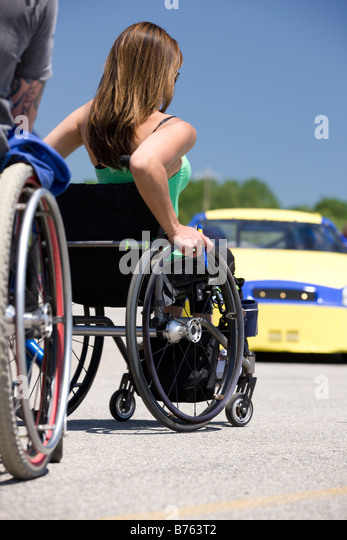 Two people on wheelchairs approaching to racing car, rear view - Stock Image