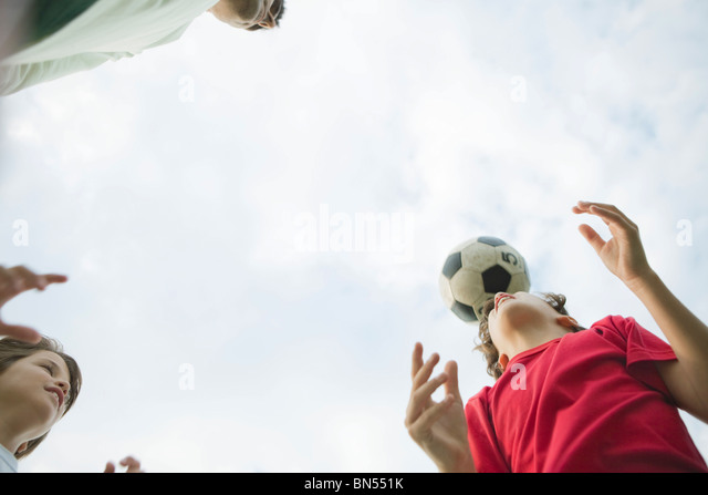 Father and sons playing soccer, low angle view - Stock Image