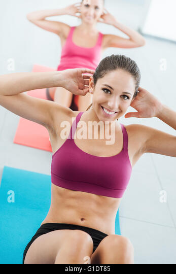 Sporty young girl at the gym doing abdominals workout on a mat, she is smiling at camera, fitness and health concept - Stock-Bilder