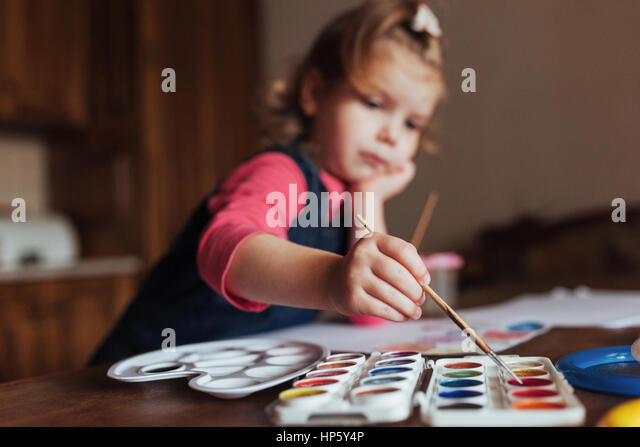 Cute happy little girl, adorable preschooler, painting with wate - Stock Image