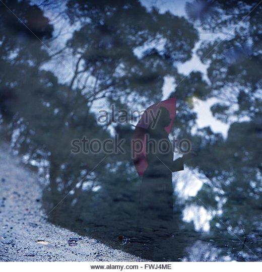 Reflection Of Woman Holding Umbrella In Puddle During Rainy Season - Stock Image