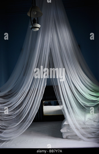White mosquito net above the bed in a hotel. - Stock-Bilder