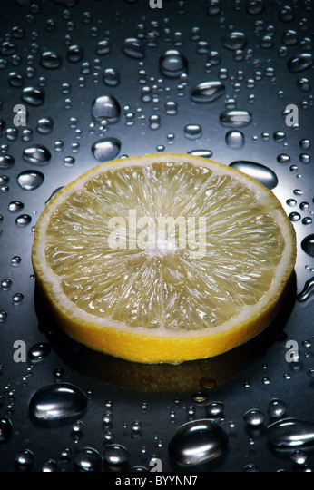 Lemon slice ,  water droplets, dramatic lighting,vertical - Stock Image