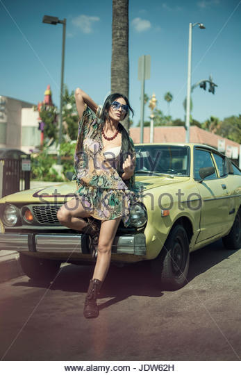 Young woman leaning against front of car - Stock-Bilder