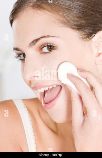 woman applying foundation with sponge - Stock Image