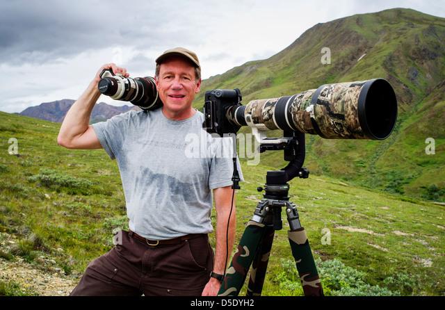 Portrait of professional photographer with large telephoto lens & tripod, Denali National Park, Alaska, AK - Stock Image