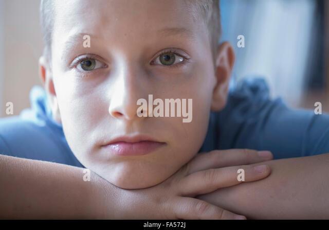 Sad boy resting head on arms, Freiburg im Breisgau, Baden-Württemberg, Germany - Stock Image