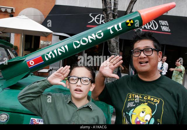 Coconut Grove Florida King Mango Strut Parade satire parody Asian father son North Korea nuclear weapon - Stock Image