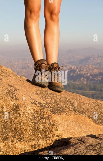 India, Karnataka, Hampi, Young woman walking on rock - Stock-Bilder