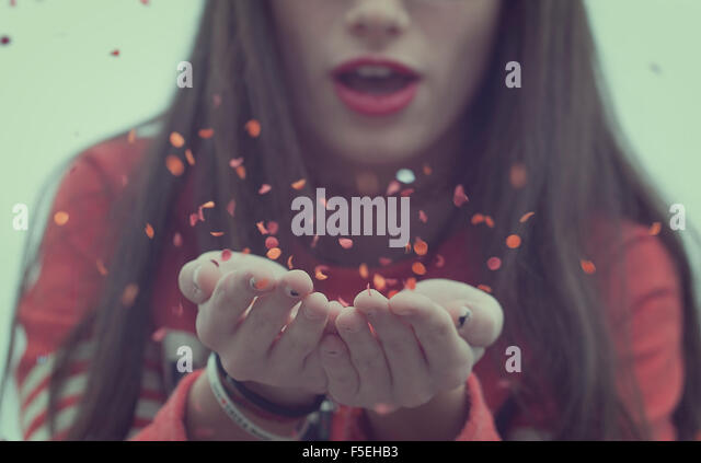 Girl blowing confetti - Stock Image