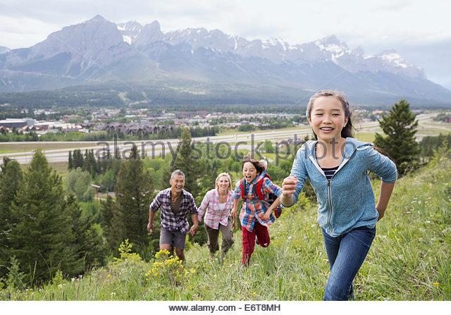Family playing on rural hillside - Stock Image