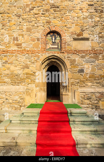 Red carpet in front of an orthodox church in Borzesti, Romania, near Onesti. The church was made by king Stefan - Stock Image