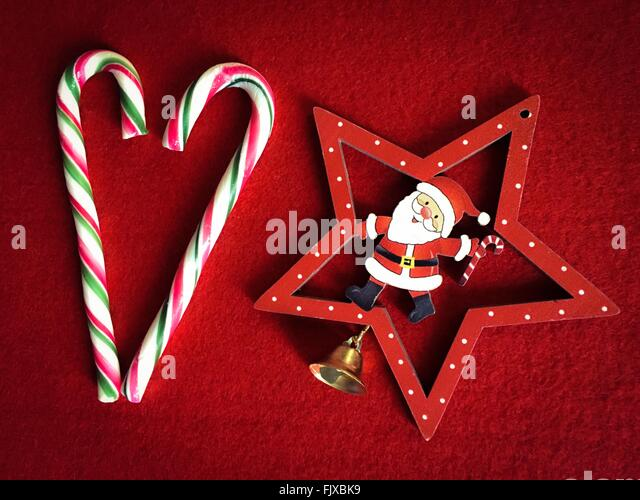 Directly Above Shot Of Candy Canes With Santa Christmas Decoration On Carpet - Stock-Bilder
