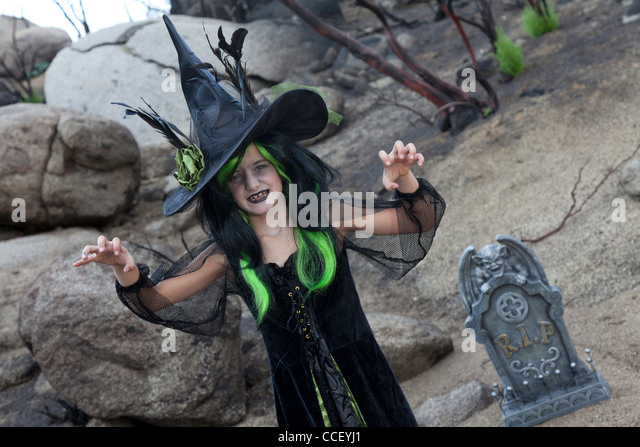 Girl in witch attire trying to scare you while standing in cemetery - Stock Image
