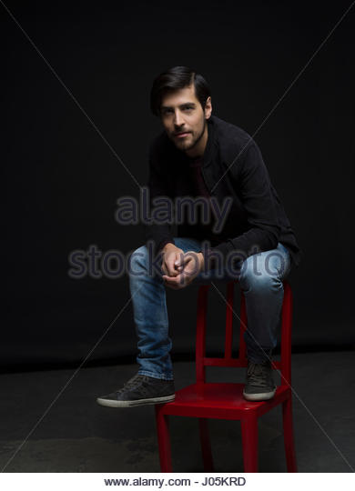 Portrait confident, cool brunette man with beard sitting on chair against black background - Stock Image