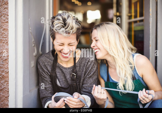 Happy fashion designers with ribbon spool sitting at studio doorway - Stock Image