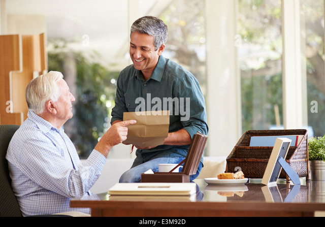 Senior Father Discussing Document With Adult Son - Stock Image