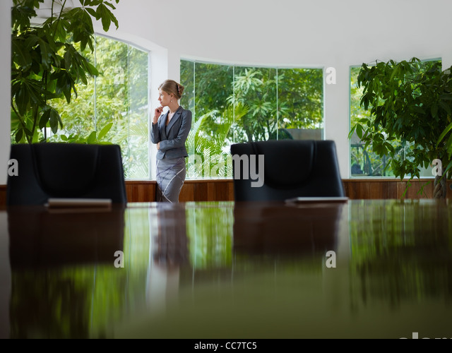 Beautiful caucasian female manager looking out of the window in office. Side view, copy space - Stock Image