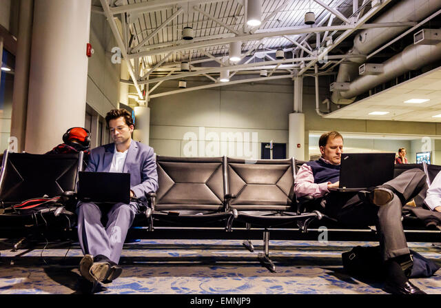 Charlotte North Carolina Charlotte Douglas International Airport CLT terminal concourse gate area man laptop using - Stock Image