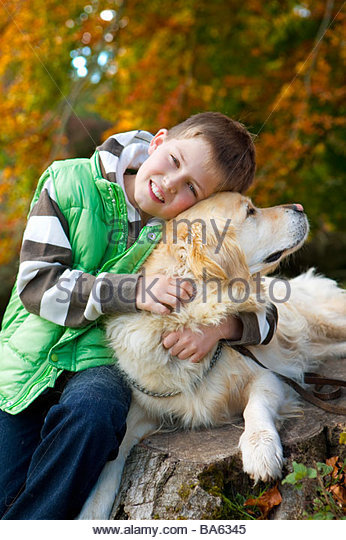 Portrait of boy hugging dog on tree stump - Stock Image