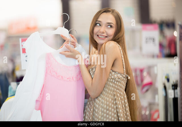 Portrait of a young pretty woman in clothing store holding two hangers with dresses in hands  looking away with - Stock Image