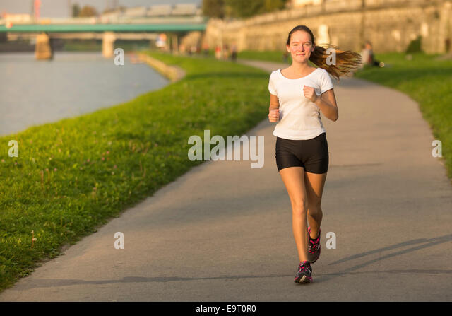 Young girl on a treadmill in the city. Healthy lifestyle. - Stock Image