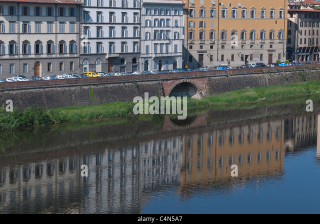 Reflections of buildings along the Arno River in early morning light in Florence, Italy. - Stock Image