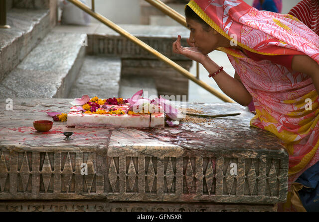A Hindu woman marks her forhead with a Tilaka or tika in Hindi at the Jagdis Temple in Udaipur, Rajistan, India. - Stock Image