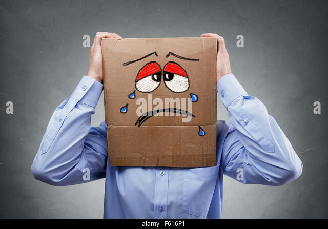 Man with cardboard box on his head showing sad expression - Stock Image