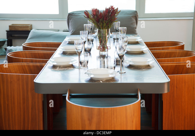 Place settings on table in luxury dining room - Stock Image