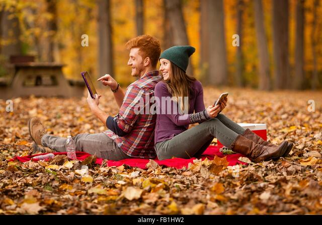 Young couple back to back using digital tablet and smartphone in forest - Stock Image