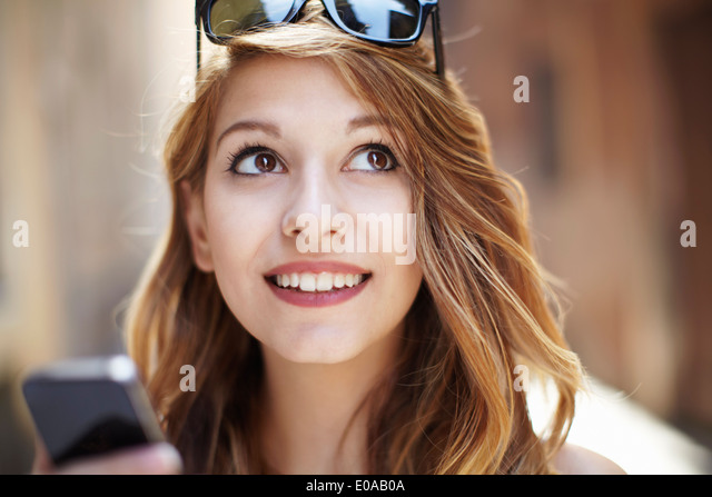 Sophisticated young woman looking up on street - Stock-Bilder