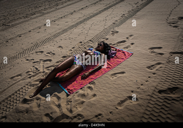 Woman sunbathing on towel on beach - Stock Image