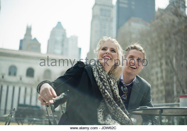 Young businesswoman and man watching from sidewalk cafe, New York City, USA - Stock-Bilder