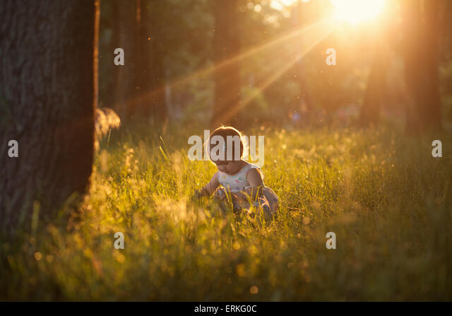 Beautiful shot of playing baby in sunset lights - Stock Image