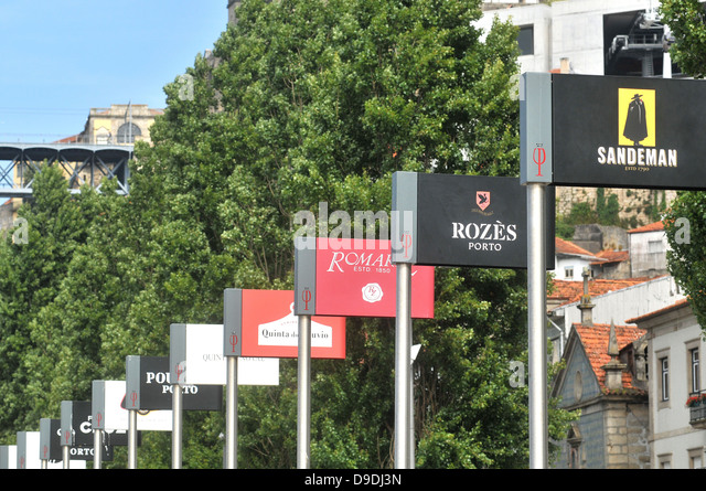 row of port wine producers' billboards on quay of Villa Nova de Gaia Portugal - Stock Image