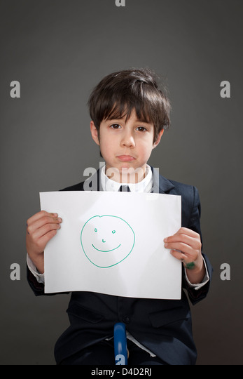 Sad boy with drawing of happy face - Stock-Bilder