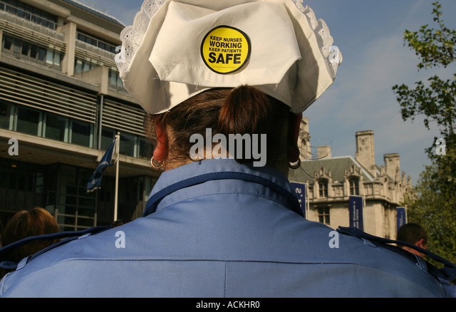 A trainee nurse at a rally in protest at changes in the NHS with a campaign sticker on her hat, Westminster, London, - Stock Image