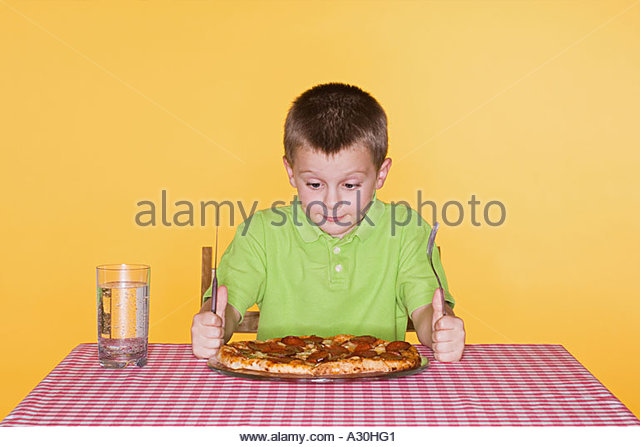 Boy about to eat a pizza - Stock-Bilder